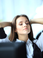 Portrait of an elegant cheerful woman relaxing in office