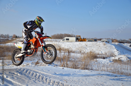 Motorcycling rider on the bike jumps from a hill on a snowy high
