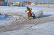 MX rider on motorcycle moves in a turnabout with skid in snow