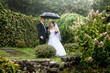 Beautiful bride and groom walking under umbrella at park