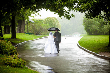 couple under umbrella walking away on road at park