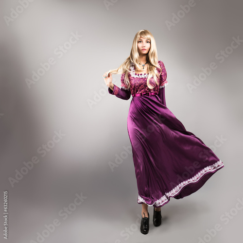 Woman in Waving Purple Dress on Gray Backgound