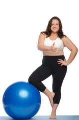 Happy woman with excess weight and ball