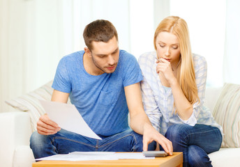 busy couple with papers and calculator at home