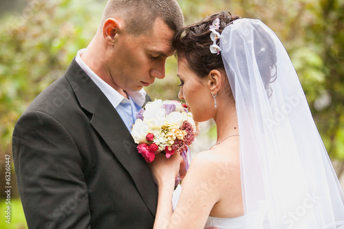 Closeup portrait of sad bride and groom looking at bouquet