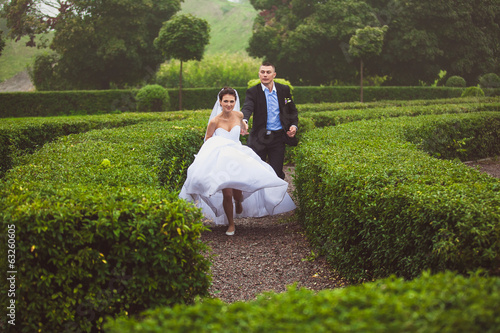 Beautiful bride and groom running at garden maze