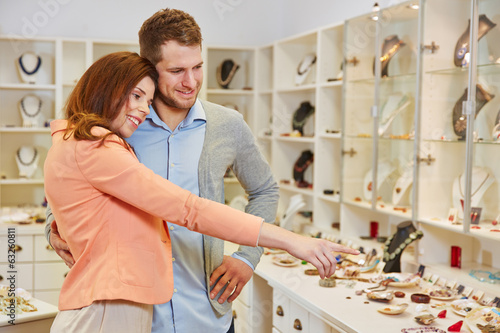 Woman showing man jewelry in store