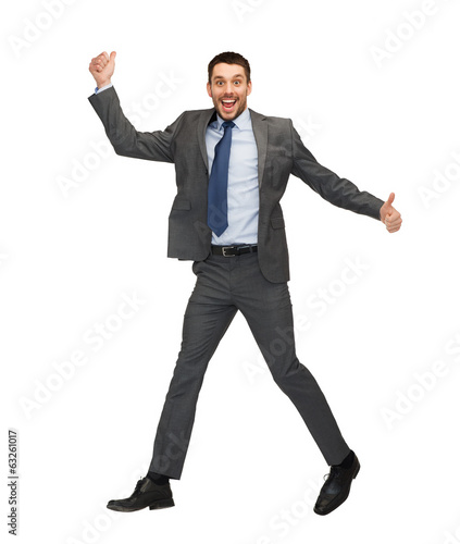 smiling businessman jumping and showing thumbs up