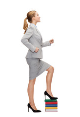 smiling businesswoman stepping on pile of books