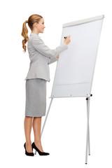 smiling businesswoman writing on flip board