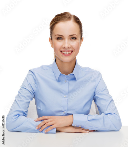young smiling businesswoman sitting at table