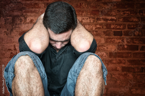 Stressed and sad young man sitting on the floor