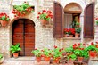 Italian house front with colorful potted flowers
