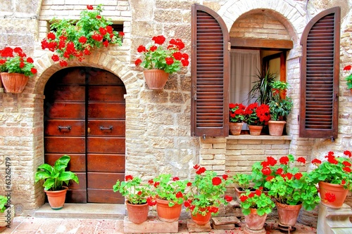 Obraz Italian house front with colorful potted flowers