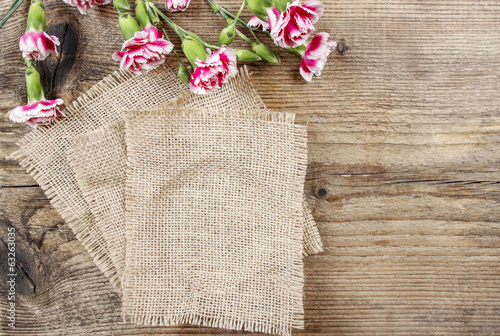 Red and white carnation flowers on wooden background. Copy space