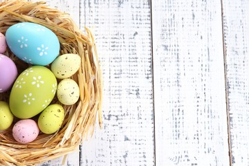 Easter eggs in nest on color wooden background
