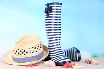 Pair of colorful gumboots and hat on bright background
