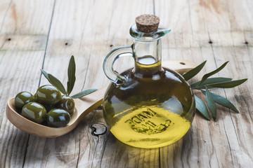 Aceite de oliva virgen y aceitunas en cuchara de madera