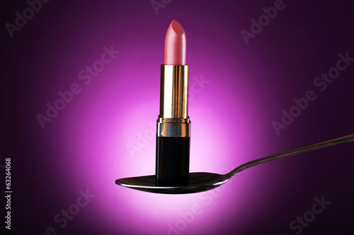 Lipstick in silver spoon on purple background