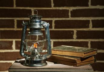 Burning kerosene lamp and books on brick wall background