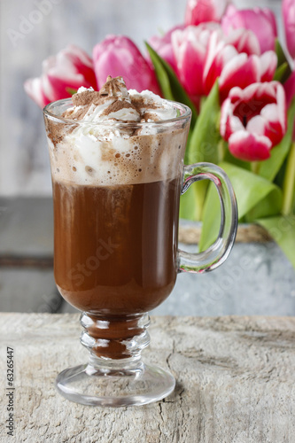 Irish coffee on wooden table. Bouquet of pink and red tulips