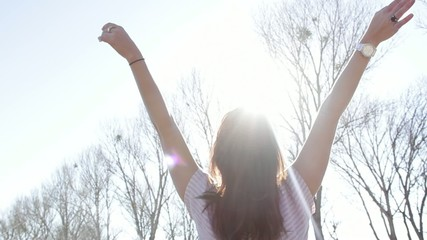 Woman in the outdoors with arms wide open under the sunlight