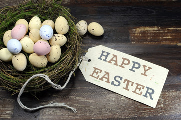 Happy Easter candy easter eggs in birds nest on dark wood.