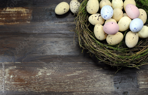 Happy Easter candy eggs in birds nest dark wood background