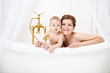 Loving mother and little son in bathtub