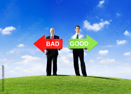 Two Businessmen Holding Contrasting Arrows for Bad and Good