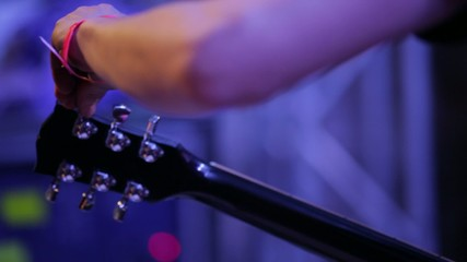 Medium shot of musician's arm tuning electric guitar