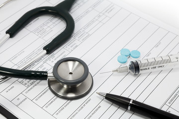 stethoscope syringe and pills on blank Patient information