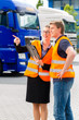 Spediteure vor Lastwagen und LKW auf Depot