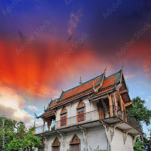 Thailand. Temple surrounded by vegetation with sunset sky on bac