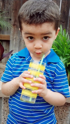 Cute mixed-race boy drinking from a cup with a straw.