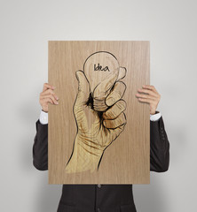man showing poster of Hand drawn light bulb with IDEA word on wo