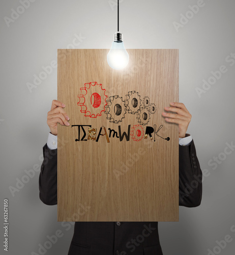 man showing poster of hand drawn word TEAMWORK with growing ligh