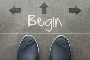 Hand drawn BEGIN design word on front of business man feet as co