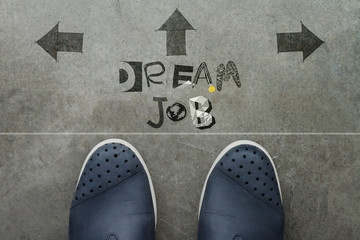 Hand drawn DREAM JOB design word on front of business man feet a