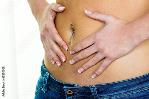 Frau hat Hände am Bauch