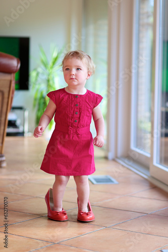 toddler girl in beautiful dress trying mom's red high heel shoes