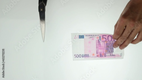 hands cutting 500 euro note