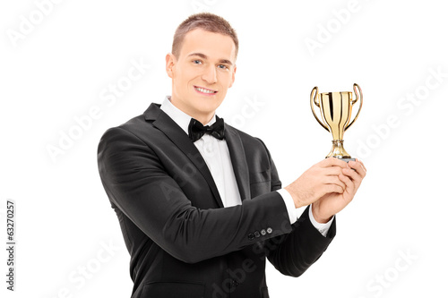 Young man in suit holding a trophy