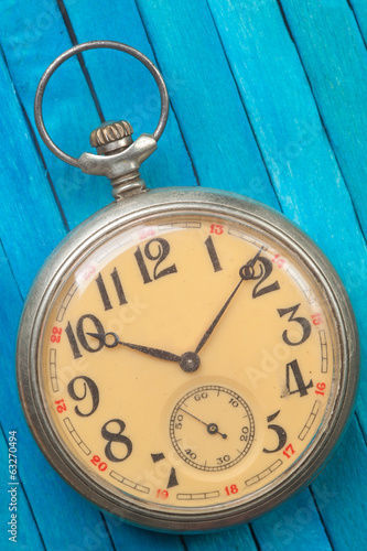 old style pocket watch on blue wooden backround