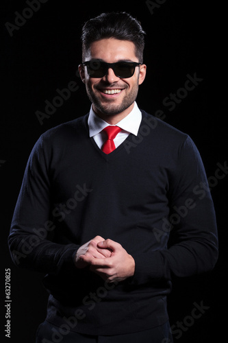 business man smiles with hands together