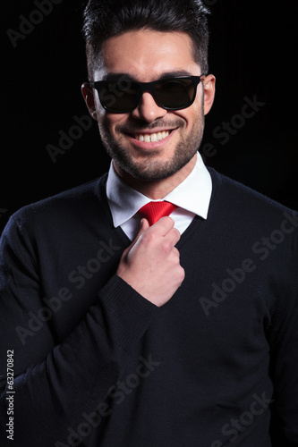 business man adjusts his tie