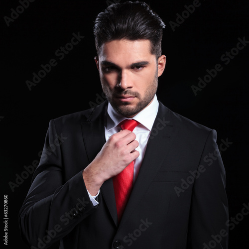 serious business man adjusts his tie