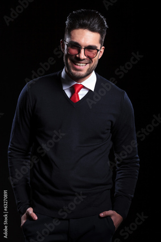 business man smiles with hands in pocket