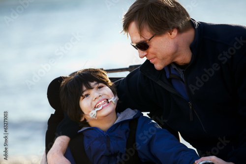 Father sitting with disabled son along lake shore