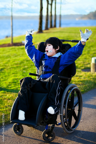 Disabled boy in wheelchair enjoying day at park